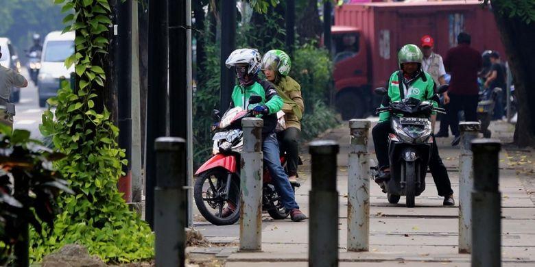 Pengendara sepeda motor yang melintasi trotoar di Jalan Kebon Sirih, Jakarta Pusat, Senin (17/7/2017). Pengendara sering memanfaatkan trotoar untuk memotong jalan agar bisa lebih cepat ketimbang melewati jalan raya.