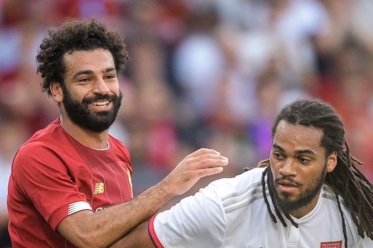 Mohamed Salah tampak tersenyum seusai berebutan bola dengan Jason Denayer pada laga Liverpool vs Lyon di Jenewa, 31 Juli 2019.