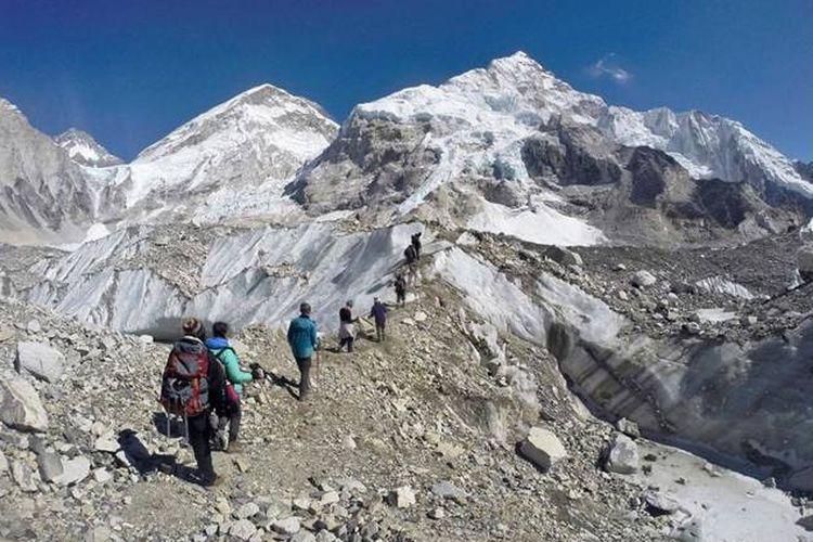 Pada hari Senin, 22 Februari 2016, para trekker melewati gletser di base camp Mount Everest, Nepal. Sepertiga dari gletser Himalaya akan mencair pada akhir abad ini karena perubahan iklim, mengancam sumber air bagi 1,9 miliar orang, bahkan jika upaya saat ini untuk mengurangi perubahan iklim berhasil, menurut penilaian yang dirilis Senin, 4 Februari, 2019 oleh Pusat Internasional untuk Pengembangan Gunung Terpadu.