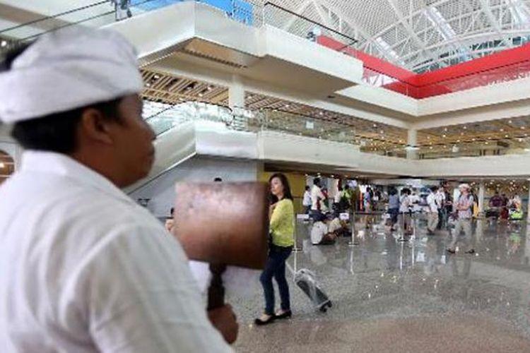 Seorang pemandu wisata menjemput wisatawan di terminal kedatangan internasional Bandara Ngurah Rai, Bali, Rabu (12/3/2014). Kunjungan wisatawan ke Bali masih terpantau ramai menjelang Hari Raya Nyepi.