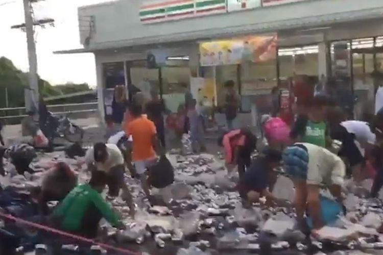 Foto tangkapan layar rekaman video yang memperlihatkan warga di Phuket, Thailand sedang mengumpulkan kaleng bir yang berserakan di jalan setelah truk pengangkutnya terbalik.