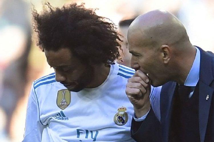 Bek kiri Real Madrid, Marcelo (kiri), sedang mendengarkan arahan dari pelatihnya, Zinedine Zidane, pada laga pekan ke-17 La Liga Spanyol melawan FC Barcelona, di Stadion Santiago Bernabeu, Sabtu (23/12/2017).