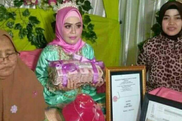 Andi Sulfaidah (30) memperlihatkan uang tunai Rp 200 juta usai dilamar Alfi Daeng Makkelo (70), Rabu (8/8/2018).