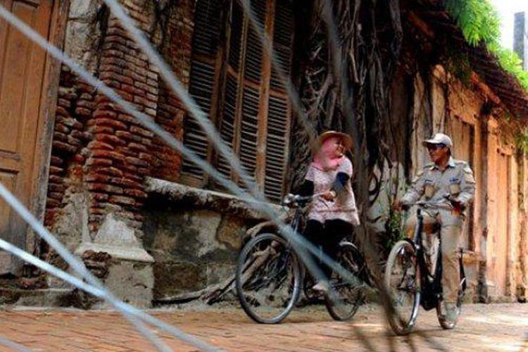 Pengunjung terlihat asyik menikmati pesona bangunan di rumah tembok akar tepatnya di depan Gedung Monod Diephuis salah satu bangunan peninggalan zaman Belanda di Kawasan Kota Lama Semarang dengan mengendarai sepeda, Jumat (11/1/2019). Rute keliling Kota lama dengan mengendarai sepeda mulai dari Taman Sri Gunting (Gereja Blenduk), Jembatan Berok, Kantor Pos, Stasiun Tawang, Cendrawasih, Gedung Marabunta dan kembali lagi ke Taman Srigunting.