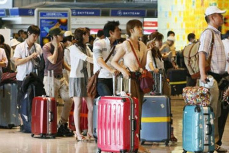 Antrean turis China di sebuah bandara.