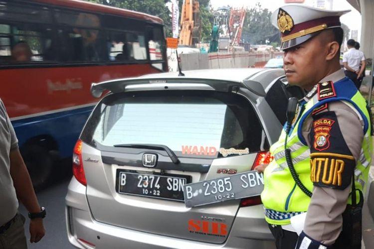 Pengemudi Honda Jazz bernama Wanda ditilang polisi karena kedapatan memiliki pelat ganda untuk menghindari aturan pembatasan kendaraan berdasarkan nomor pelat ganjil dan genap di Jalan Gatot Subroto, simpang Pancoran, Jakarta Selatan, Rabu (1/8/2018).