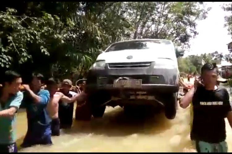 Tangkapan layar video saat warga menggotong mobil untuk menerobos banjir di Kecamatan Kayan Hilir, Kabupaten Sintang, Kalimantan Barat
