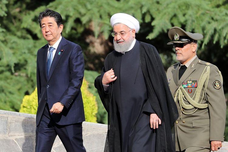 Presiden Iran Hassan Rouhani (tengah) menyambut Perdana Menteri Jepang Shinzo Abe (kiri) yang datang berkunjung ke Teheran, Rabu (12/6/2019).