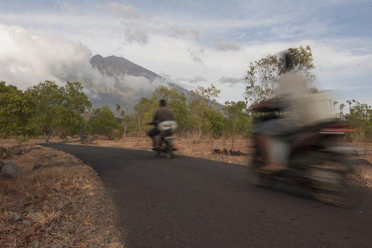 Sejumlah warga melintas di jalan Desa Datah yang berjarak sekitar 10Km dari kawah Gunung Agung, Karangasem, Bali, Minggu (8/10/2017). Pusat Vulkanologi dan Mitigasi Bencana Geologi mencatat aktivitas Gunung Agung kembali meningkat yang disertai semburan asap putih dengan tinggi hingga 1.000 meter dari kawah sejak Sabtu (7/10/2017) malam.