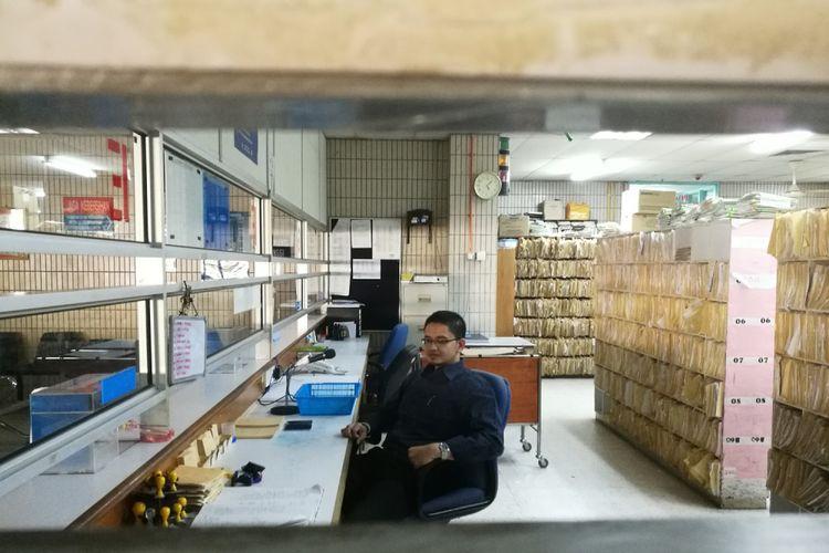 Dr Prashanth duduk di ruang pengarsipan.