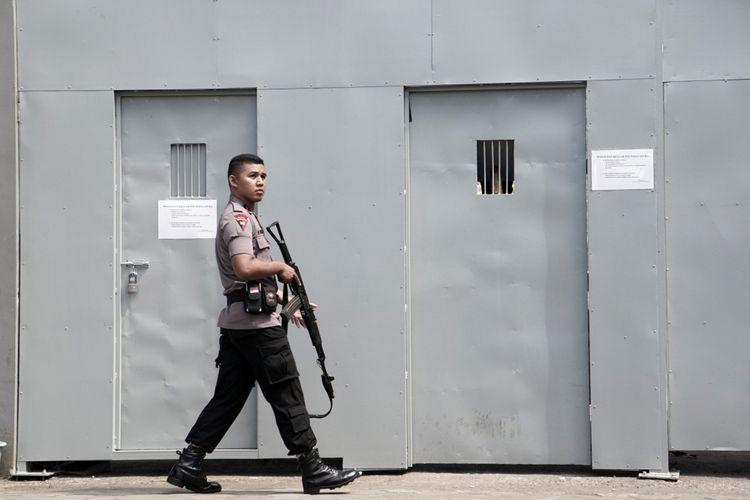 Seorang polisi Indonesia menjaga di luar gerbang besi di pelabuhan Cilacap, satu-satunya gerbang ke penjara tertinggi Nusakambangan Indonesia di Cilacap pada 25 Juli 2016.