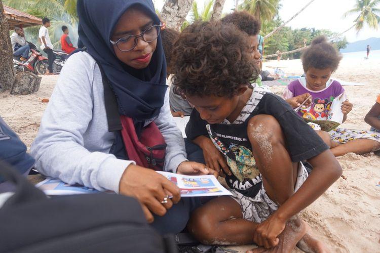 Fauzhya (berkacamata) sedang mengajar membaca di salah satu distrik di Fakfak, Papua Barat.