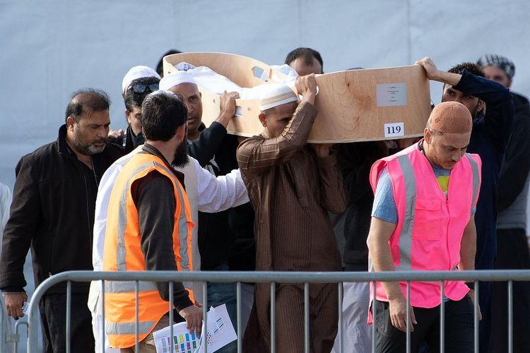 Para pelayat membuat sebuah peti berisi salah satu jenazah korban penembakan di masjid Christchurch, Selandia Baru, untuk dibawa ke Pemakaman Christchurch pada Jumat (22/3/2019).