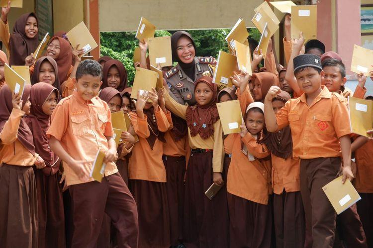 Satlantas Polres Aceh Besar AKP Vifa membagikan buku kepada anak-anak sekolah dasar di pulua terluar Kabupaten Aceh Besar.