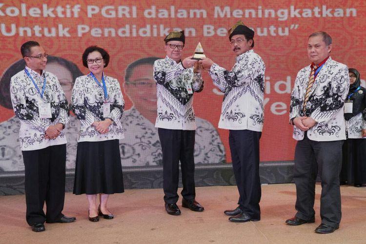 Menteri Dalam Negeri Tjahjo Kumolo menerima cinderamata dari Gubernur Kepulauan Riau Nurdin Basirun usai membuka Konferensi Kerja Nasional (Konkernas) ke-5 PGRI di Kota Batam, Kepulauan Riau, Jumat (2/2/2018).