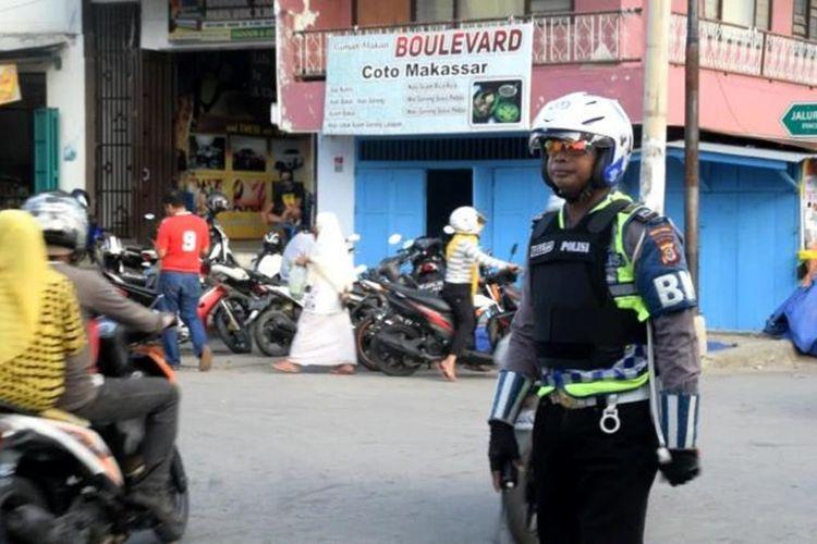 Bripka Muhamad Fitrah, Anggota Satlantas Polres Baubau, mengatur lalu lintas di Pasar Karya Nugraha, Sabtu (19/5/2018) sore