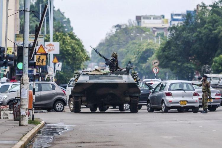 Tentara Zimbabwe dengan sebuah kendaraan lapis baja berjaga di sebuah perempatan jalan di ibu kota Harare, Rabu (15/11/2017).