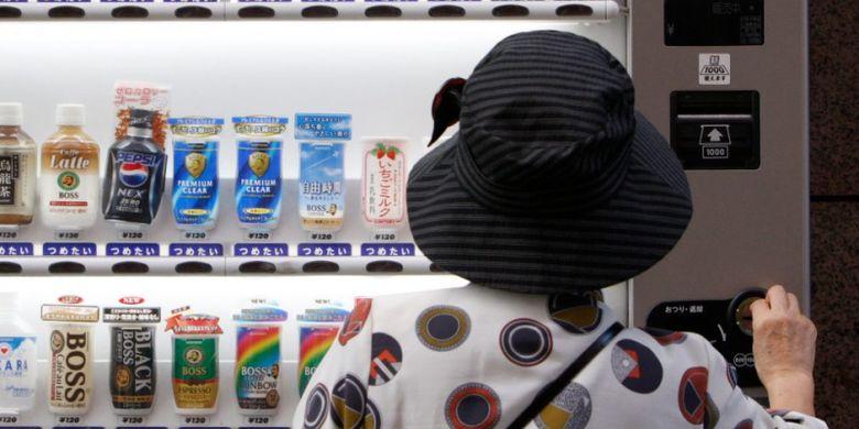 Seorang wanita tengah membeli minuman dari mesin penjual otomatis di Jepang.