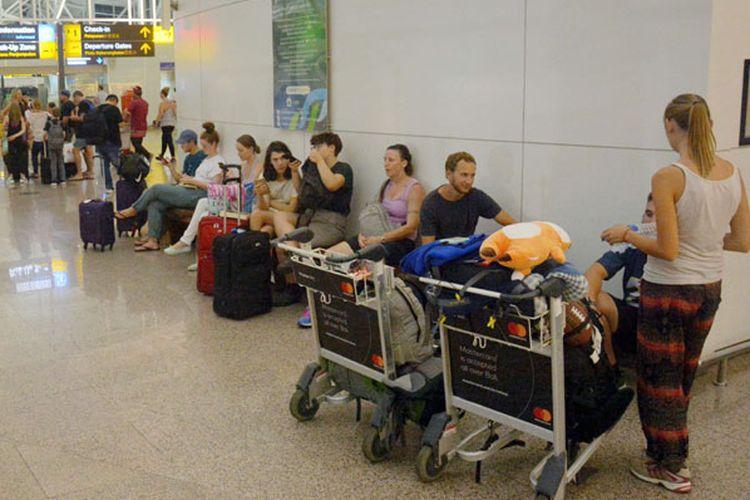 Sejumlah penumpang menunggu jadwal penerbangan di Terminal Internasional Bandara Ngurah Rai, Bali, Kamis (28/6/2018). Sebanyak 3.571 penumpang dari 26 maskapai penerbangan domestik dan internasional terpaksa batal terbang karena dampak erupsi Gunung Agung yang terjadi pada Kamis (28/6/2018).