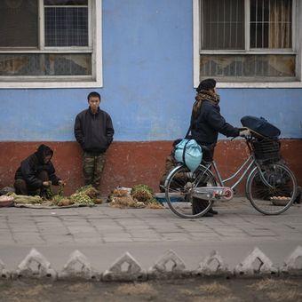 Foto ini diambi pada 30 November 2016 menunjukkan orang-orang menjual buah dan sayur di jalan Kaesong, Korea Utara. (AFP/Ed Jones)
