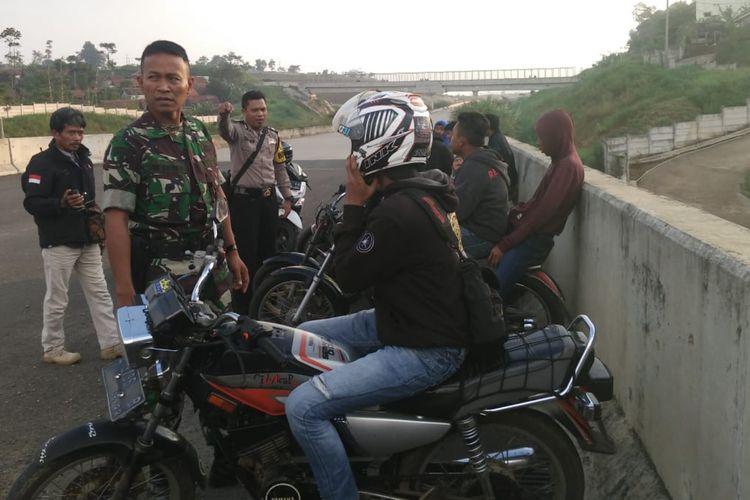 Babinsa dan Bhabinkamtibmas Pamulihan memberikan arahan kepada sejumlah pemuda yang kedapatan melakukan aksi balapan liar di lokasi Tol Cisumdawu, Sumedang, Jawa Barat, Selasa (7/5/2019). AAM AMINULLAH/KOMPAS.com