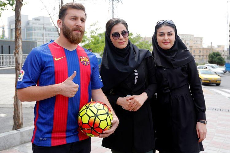 Reza Parastesh, sang kembaran Lionel Messi, sedang berpose bersama dengan dua orang gadis Iran.