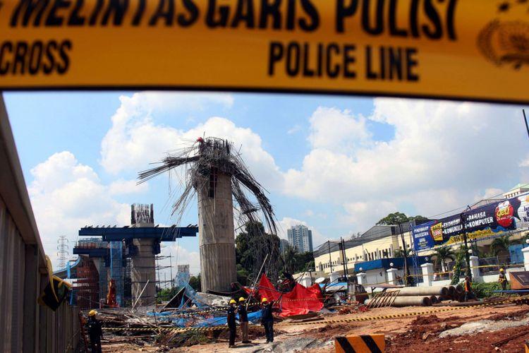 Petugas dari kepolisian mengecek kondisi pasca robohnya cetakan beton tiang pancang proyek Jalan Tol Becakayu, di Jalan DI Panjaitan, Jakarta, Selasa (20/02/2018). Peristiwa tersebut terjadi pada pukul 03.00 WIB saat pekerja sedang melakukan pengecoran. Terdapat tujuh korban yang dilarikan ke Rumah Sakit UKI dan Polri.