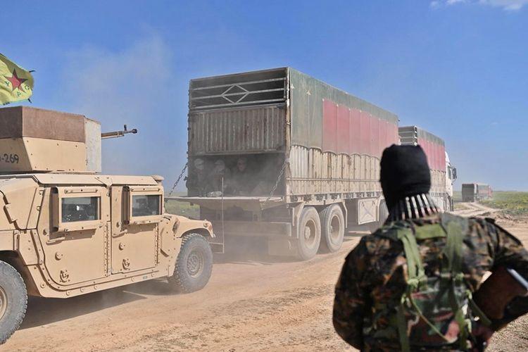 Anggota pasukan Kurdi Suriah bersiaga sementara konvoi truk membawa warga sipil keluar dari benteng terakhir ISIS di Desa Baghouz, Rabu (20/2/2019).