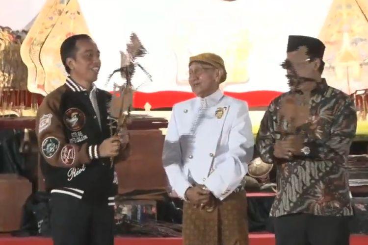 Presiden Jokowi lalu menerima sebuah wayang dari sang dalang Ki Manteb Soedharsono, dalam pagelaran wayang di halaman Istana Merdeka, Jakarta, Jumat (2/8/2019).. Jokowi yang mengenakan jaket bomber berwarna biru sempat memainkan wayang tersebut. (Biro pers setpres)