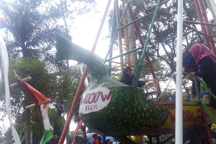 Wisatawan sedang menaiki wahana rekreasi anak di Kawasan Waduk Darma Kuningan.