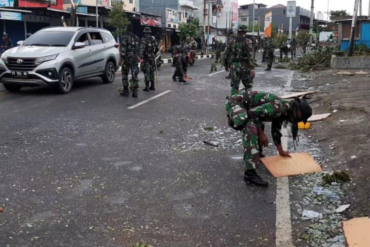 Aparat TNI AD sedang membersihkan pecahan kaca yang masih berserakkan di ruas Jalan Yos Sudraso, pasca-kerusuhan di Manokwari, Selasa (20/8/2019).(KOMPAS.com/ BUDY SETIAWAN)