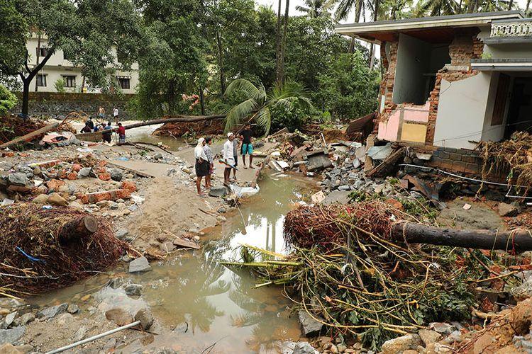 Warga menyaksikan sebuah rumah yang hancur setelah diterjang banjir di Kannappankundu di Kozhikode, negara bagian Kerala, India.