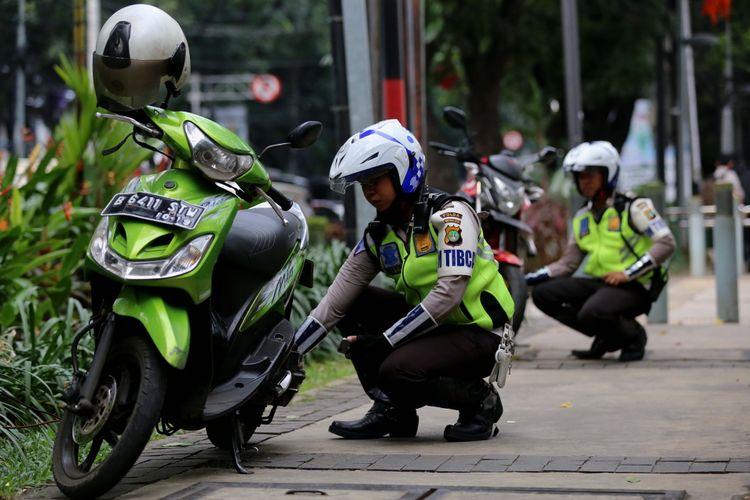 Polisi menggembosi ban sepeda motor yang parkir sembarangan di Jalan Kebon Sirih, Jakarta Pusat, Senin (17/7/2017). Pengendara sering memanfaatkan trotoar untuk memotong jalan agar bisa lebih cepat ketimbang melewati jalan raya.