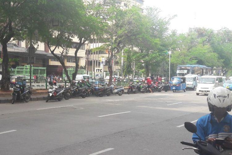 Sejumlah sepeda motor milik pengemudi ojek online diparkir di tepian jaur Transjakarta di Mangga Dua, Jakarta Utara, Minggu (15/4/2018).