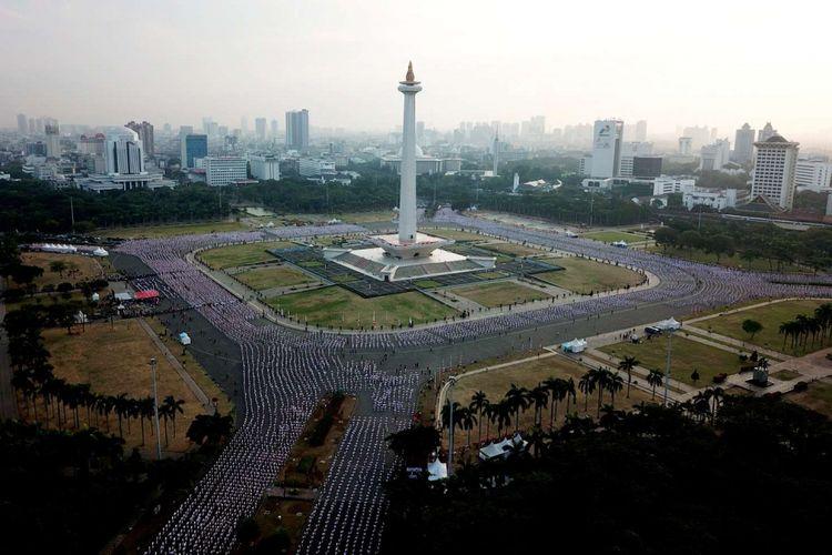 Ribuan warga melakukan senam poco-poco saat pemecahan rekor dunia senam massal poco-poco di Monas, Jakarta, Minggu (5/8/2018). Kegiatan dalam rangka menyambut Asian Games 2018 itu diikuti 65 ribu peserta dari berbagai kalangan.