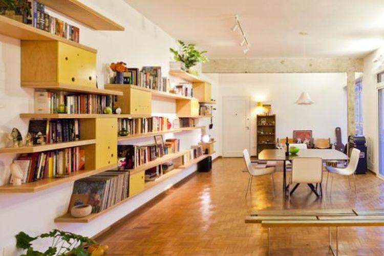 Satu-satunya fitur yang menguasai ruang tersebut hanyalah rak buku di dinding. Rak tersebut menggunakan aksen yang sama dengan dapur, yaiu lemari-lemari berwarna kuning dengan bolongan-bolongan mungil tersebar di permukaannya.