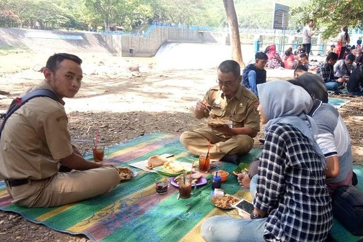 Warga menikmati makanan di pinggir Bendungan Kramat di Batang, Jawa Tengah, Selasa (11/6/2019).