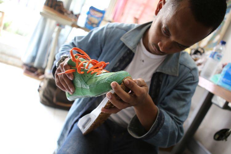 Fajri Dimyati alias Ibo -pemilik KrideLab, harus melekatkan dengan teliti bidang sol baru dengan sneakers Nike Air Max 90 Homegrown yang sedang direparasi dengan mekanisme sole swap.