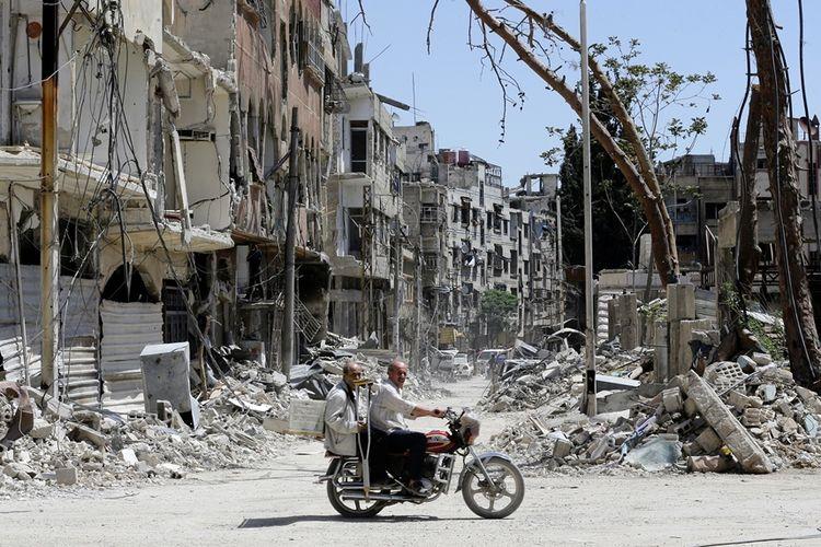 Warga Suriah mengendari sepeda motor melintasi kawasan yang rusak di kota Douma, Senin (16/4/2018).