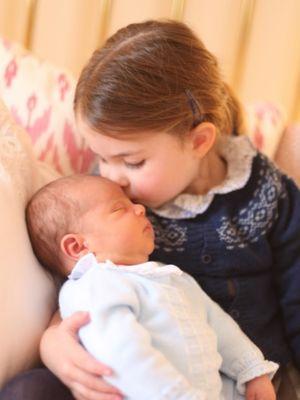 Foto yang dirilis Kerajaan Inggris, Minggu (6/5/2018), menampilkan anak kedua Pangeran William dengan Kate Middleton, Putri Charlotte sedang mencium adik laki-lakinya, Louis Arthur Charles.