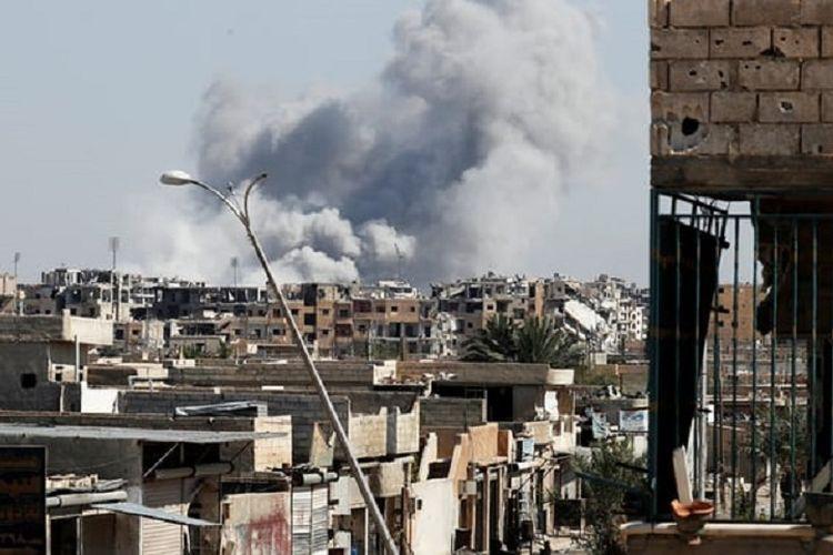 Asap mengepul di dekat stadion di kota Raqqa, Suriah utara, di mana pasukan ISIS bersembunyi setelah serangan udara kolaisi AS menghancurkan kawasan itu pada Kamis (12/10/2017)