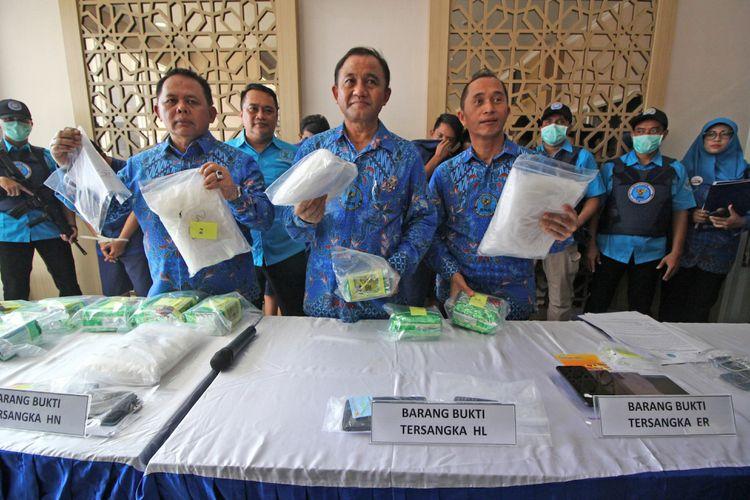 Kepala Badan Narkotika Nasional (BNN) Komjen Pol Heru Winarko (tengah), Direktur Tindak Pidana Pencucian Uang (TPPU) Brigjen Pol Bahagia Dachi (keempat kanan) dan Kepala BNN Provinsi Jawa Timur Brigjen Pol Bambang Budi Santoso (ketiga kiri) menunjukkan barang bukti saat ungkap kasus narkoba jenis sabu di Surabaya, Jawa Timur, Jumat (8/2/2019). BNN menangkap tujuh orang tersangka berinisial AD (39), ER (33), F (35), HL (44), I (55), HN (31) dan WS (23) dan mengamankan barang bukti narkotika jenis sabu seberat 18,3 kilogram yang dibeli dari Malaysia melalui Dumai, Provinsi Riau untuk diedarkan ke Madura. ANTARA FOTO/Moch Asim/ama.