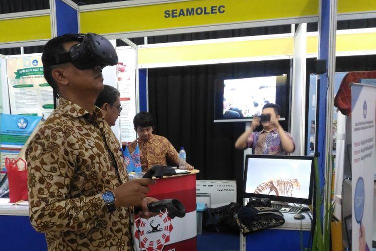 Seorang guru mencoba teknologi visual reality yang memaparkan materi pembelajaran pada pameran Hari Guru Nasional 2017 di kantor Kemdikbud. Penggunaan teknologi dalam dunia pendidikan mesti terus ditingkatkan untuk mewujudkan generasi emas pada 2045.