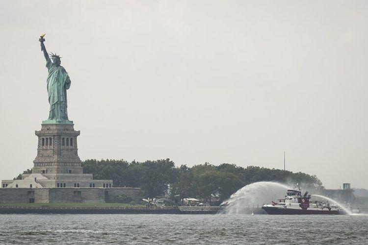 Kapal pemadam dari Departemen Pemadam Kebakaran New York menyemprotkan air ke lokasi kebakaran di dekat patung Liberty, Senin (27/8/2018).