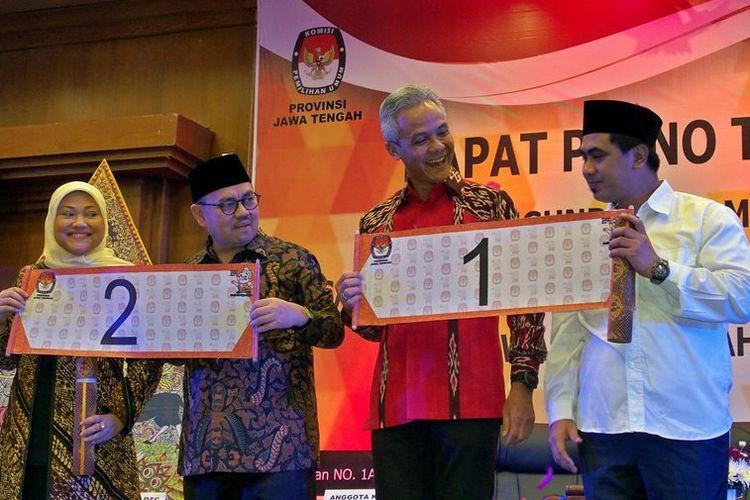 Pasangan cagub-cawagub Jateng Ganjar Pranowo (kedua kanan)-Taj Yasin (kanan) dan Sudirman Said (kedua kiri)-Ida Fauziah (kiri) memperlihatkan nomor urut masing-masing saat pengundian nomor urut di Semarang, Jawa Tengah, Selasa (13/2). Ganjar Pranowo-Taj Yasin mendapat nomor urut satu, dan Sudirman Said-Ida Fauziah memperoleh nomor urut dua.