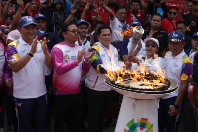 Menteri BUMN, Rini Soemarno bersama Dirut Telkomsel, Ririek Adriansyah (dua paling kanan) menyalakan replika couldron Asian Games di kantor Telkomsel Bandar Lampung, Rabu (8/8/2018).