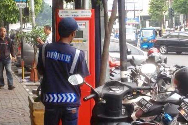 Seorang petugas sedang mendaftarkan kendaraan yang hendak parkir di Jalan Sabang, Jakarta Pusat, ke mesin parkir meter, Kamis (3/5/2017).