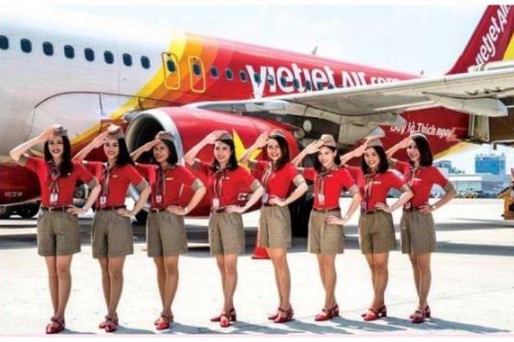 Para pramugari VietJet mengenakan sragam setelan baju merah berkerah dan celana pendek coklat.