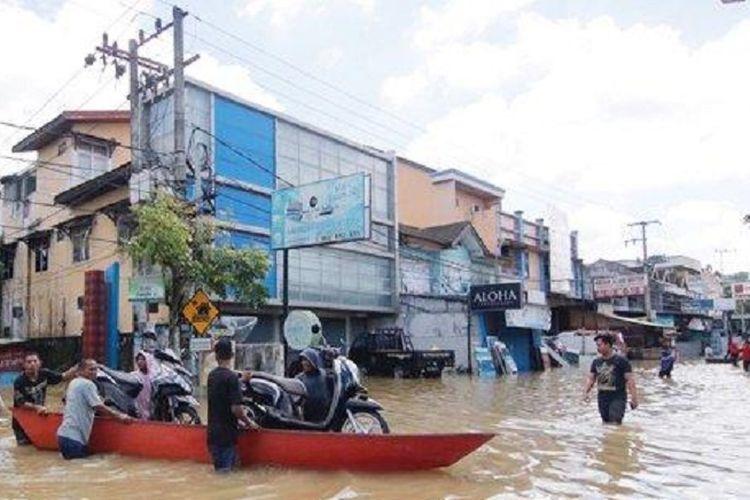 Kendaraan bermotor milik warga diangkut menggunakan perahu akibat banjir yang menutup Jalan Ahmad Yani, Samarinda, Senin (10/6/2019).