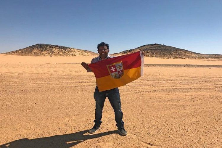 Suyash DIxit membentangkan bendera negara baru yang diproklamirkannya di Bir Tawil, sebuah wilayah tak bertuan antara Mesir dan Sudan.